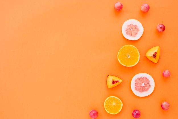 オレンジのフルーツスライス。グレープフルーツとピーチ、オレンジ色の背景上のブドウ