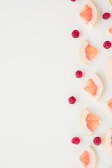 Ломтик грейпфрута и малина, изолированные на белом фоне