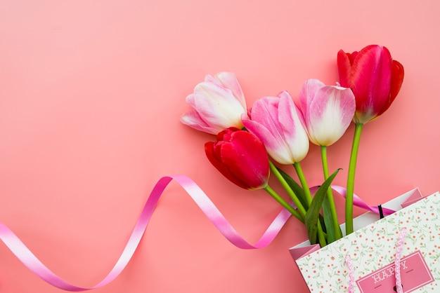ピンクの背景の上にバッグの花の花束とギフト