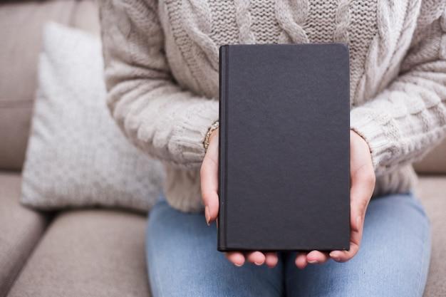 本の表紙のテンプレートを保持している女性