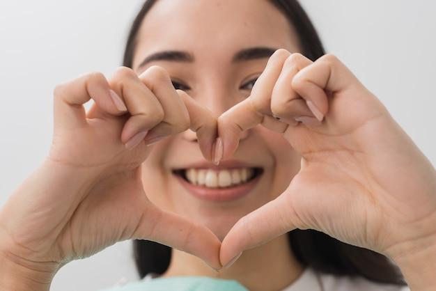 手でハート形を形成する歯科医