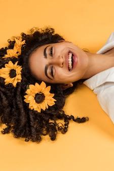 髪に花を持つ魅力的な陽気な女性