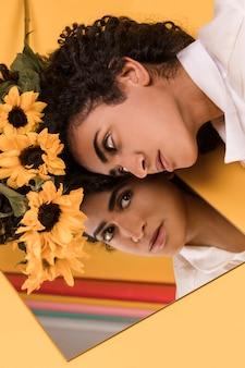 鏡の近くの髪に花を持つ魅力的な民族女性