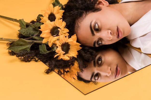 鏡で見ている花を持つ魅力的な民族のロマンチックな女性