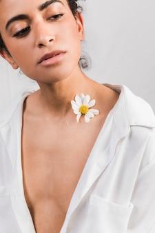 Привлекательная грустная женщина с цветком возле шеи
