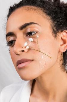 Нежная женщина с мокрым цветком на лице