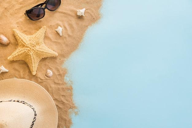 サングラスと砂の上の貝殻の近くの帽子
