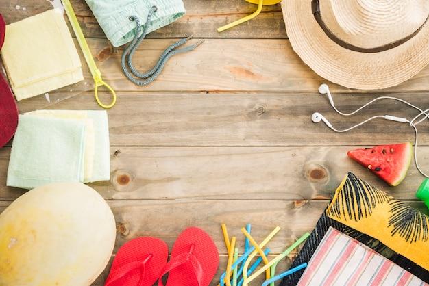 イヤホンの近くの帽子とフルーツと真空バッグ付きビーチサンダル