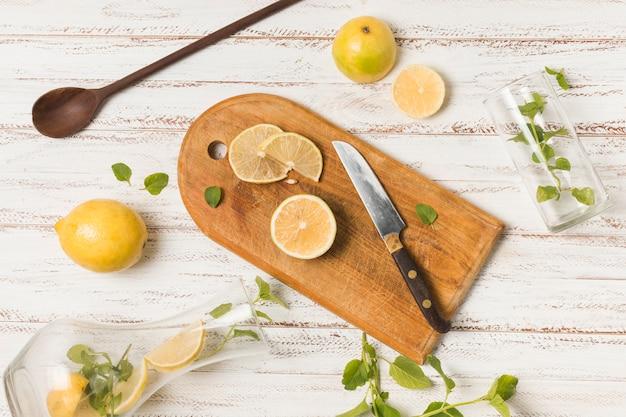 ハーブとグラスの間のナイフの近くの果物のスライス