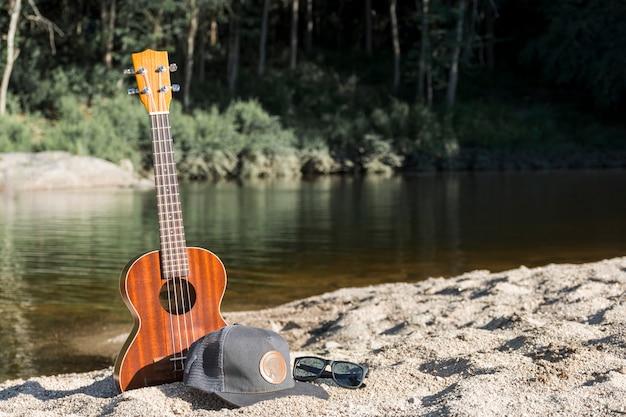 キャップとサングラスを水の近くの海岸でギター