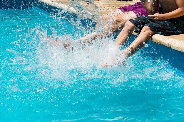 プールの端に水の飛沫の中で男性