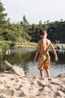 水の近くの砂の海岸の上の少年
