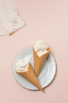 ナプキンの近くの皿の上のアイスクリームとワッフルコーン