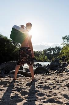川の近くの砂の海岸にクールなボックスを持つ男性