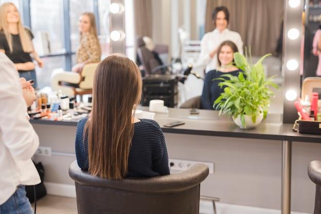 ブルネットの女性は彼女の髪を成し遂げる