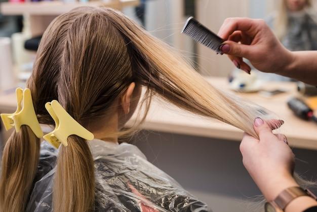 彼女の髪を成し遂げるブロンドの女の子