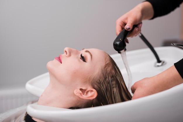 彼女の髪を洗ってもらっているブロンドの女の子