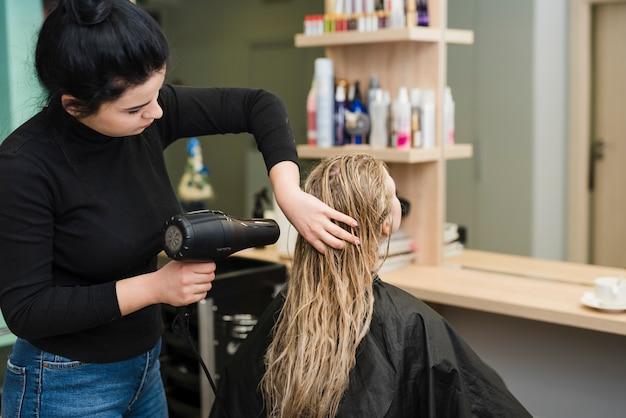 彼女の髪を乾かしているブロンドの女の子