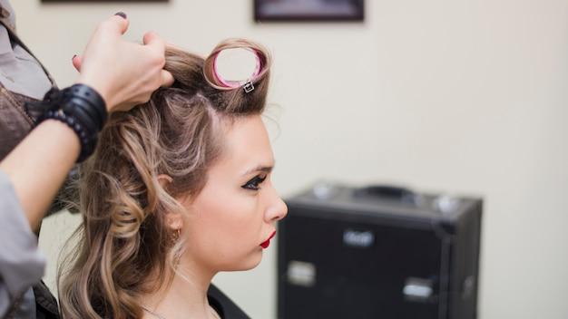 彼女の髪を成し遂げる金髪の女性