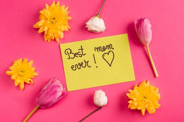 花と黄色い紙の上の最高のお母さん今までの碑文