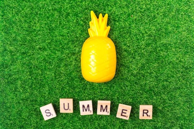 プラスチック製のおもちゃパイナップルと草の上の手紙