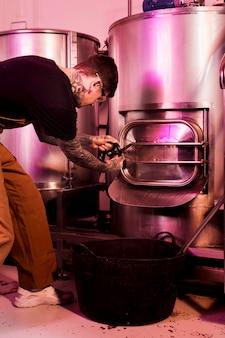 Мужчина с татуировками производит крафтовое пиво