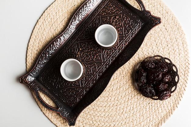 Чашки на подносе возле блюдца со сладким черносливом на коврике