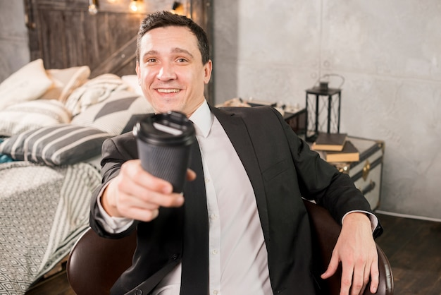 紙コップでコーヒーを提供しているハンサムな男性