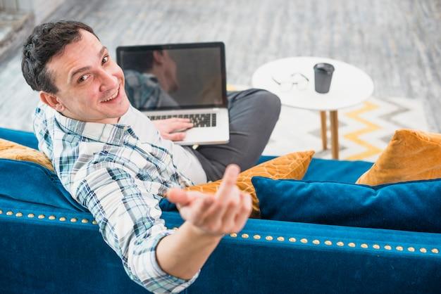 Веселый человек, сидя на диване с ноутбуком