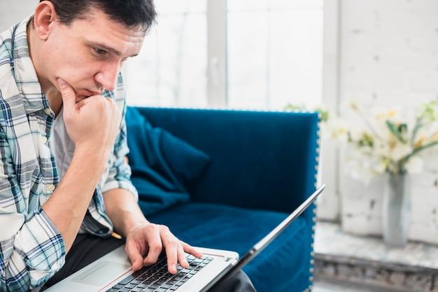 Внимательный мужчина смотрит на ноутбук у себя дома
