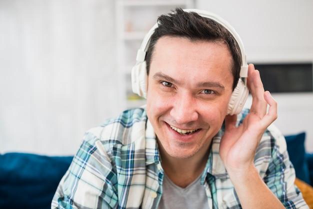 笑みを浮かべて男がソファの上にヘッドフォンで音楽を聴く