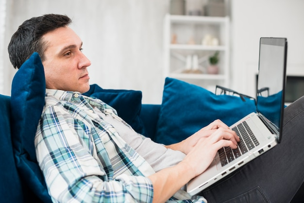 Человек печатает на ноутбуке и сидит на диване