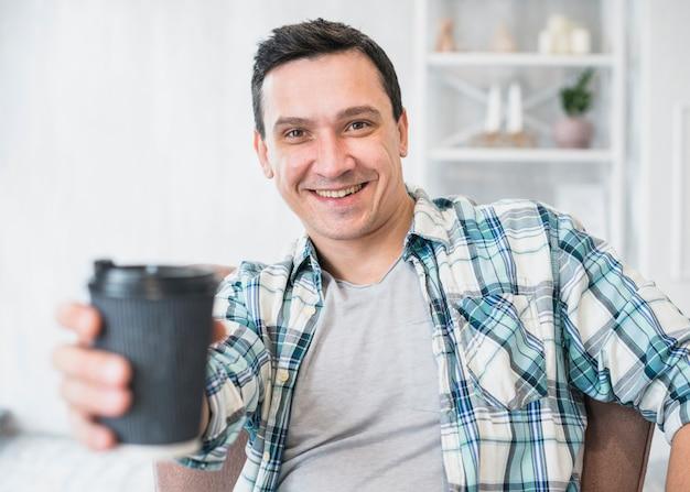 Улыбающийся человек, держащий чашку напитка на стуле у себя дома