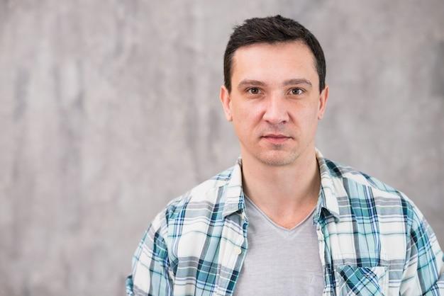 カメラ目線のフランネルシャツの後ろ髪を持つ若い男