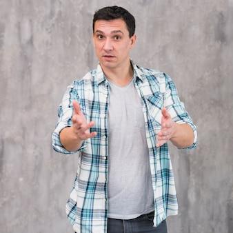Молодой удивленный парень стоя и указывая на камеру