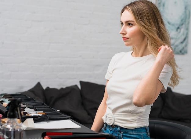 Молодая женщина поправляет прическу в студии