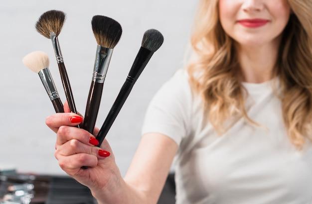 Улыбающаяся женщина-визажист держит косметические кисти