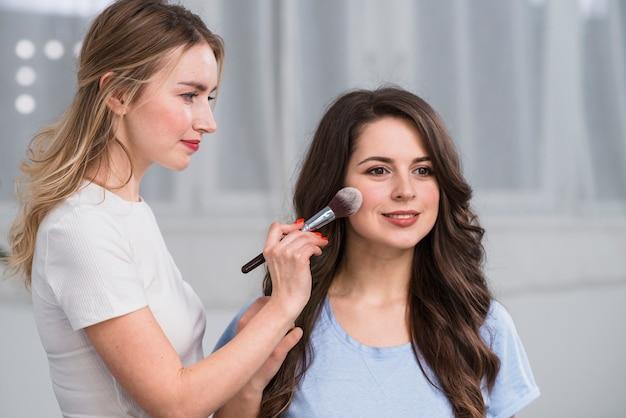 モデルの顔を粉で覆っているメイクアップアーティスト