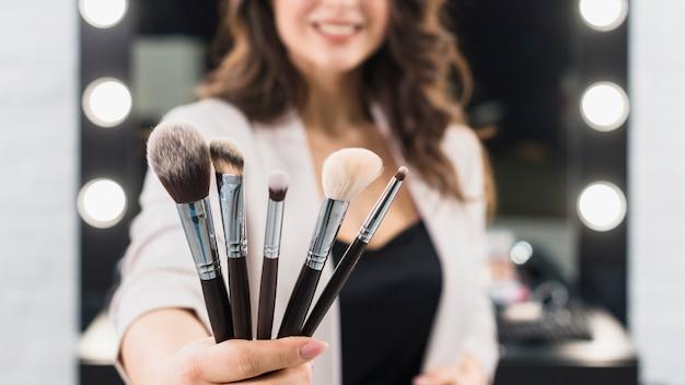 Женщина показывает макияж кисти на фоне зеркала