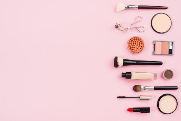ピンクの背景に化粧品および化粧品美容製品