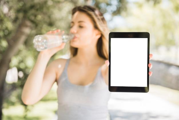 Спортивная девушка показывает планшет