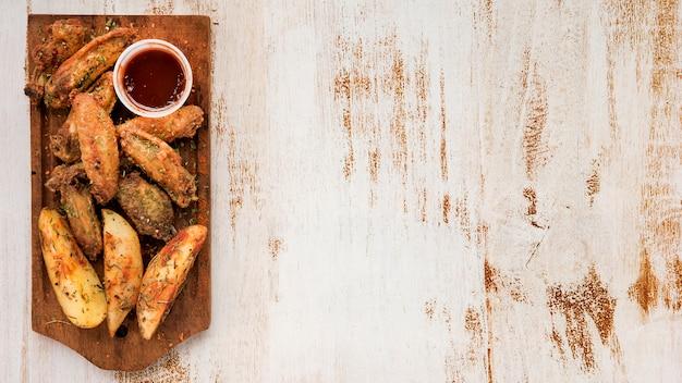 Картофельные дольки и жареные крылышки с соусом