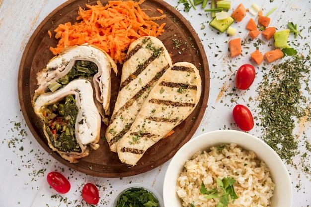 Куриный рулет и грудка на деревянной тарелке с кусочками овощей