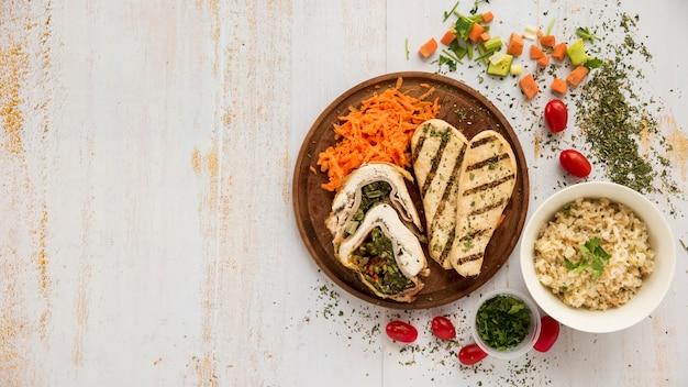 鶏肉と野菜のグランジ木製机の上の健康的な料理