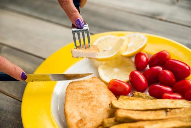 女性のフライドチキンを皿に切る