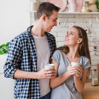 お互いを見て台所で一緒に恋に幸せなカップル