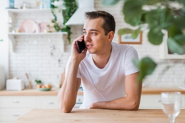 ハンサムな男が台所で電話で話す