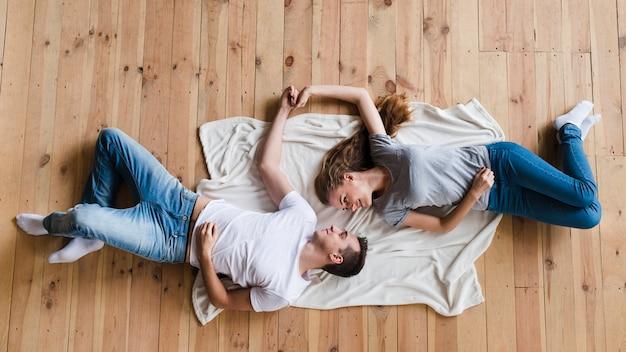 床のシートに手を繋いでいるカップル