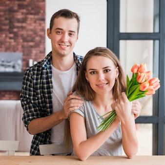 Счастливая пара с цветами, улыбаясь в камеру
