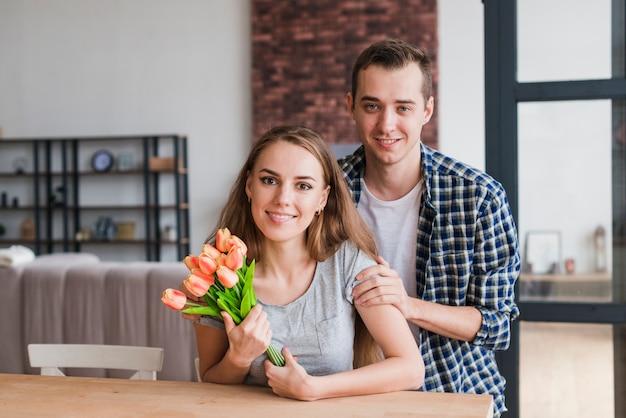 Красивый мужчина обнимает жену с красивыми цветами